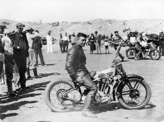 Percy Coleman sits astride a Royal Enfield motorcycle at a beach racing meet held at Waikanae Beach by the Ixion Motorcycle Club, around 1930